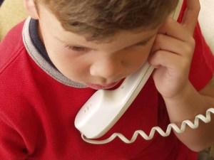 Niño hablando por teléfono.